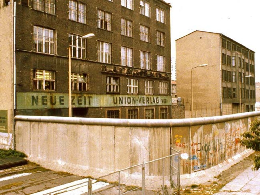 Large exterior of east berlin neue zeit  east germany  newspaper building  from the rear   with berlin wall in foreground  1984  george louis
